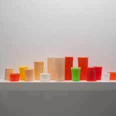 George Stoll Untitled (15 tumblers on a 36 inch shelf #3) 2002 beeswax, paraffin and pigment on a painted wooden shelf 8 ¾ x 36 x 7 ½ inches https://www.georgestoll.net/